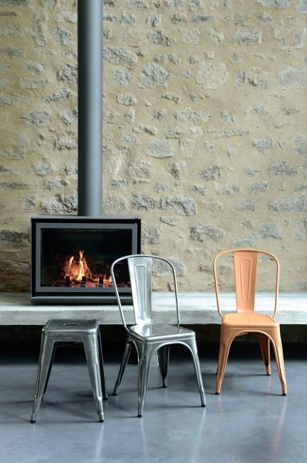 Металлические стулья и табурет Tolix у камина в загородном доме